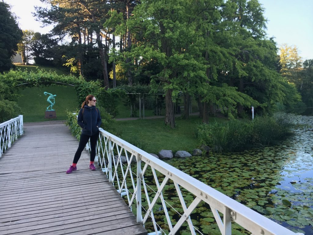 woman in all black wearing pink shoes stands on a white wood bridge over a pond