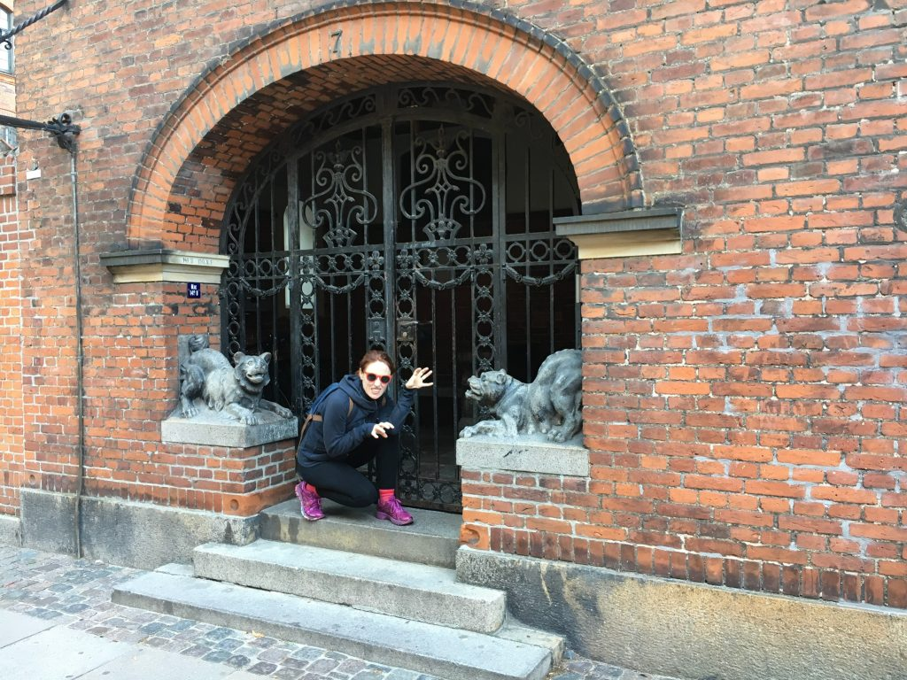 redhead in black clothes and pink shoes poses like a gargoyle in a brick doorway.