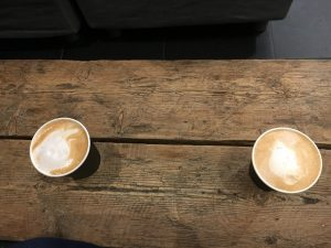 an overhead shot: two lattes sit on a wood slatted table