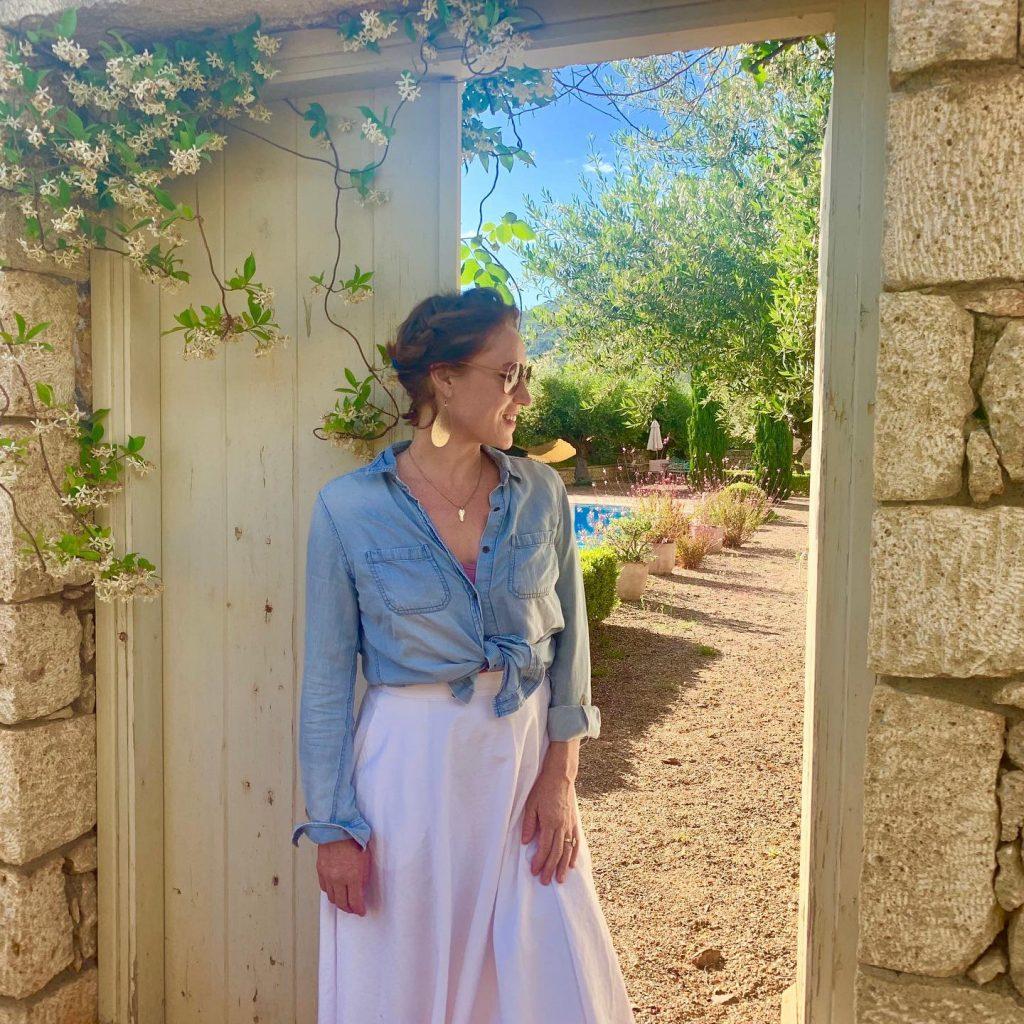 Woman standing in stone door way with sun shining through the door