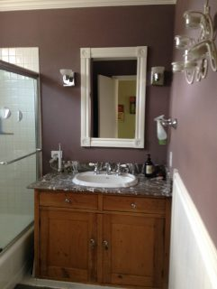 Weathered wood vanity with grey and white quartz top. White wood mirror and mauve bathroom walls.