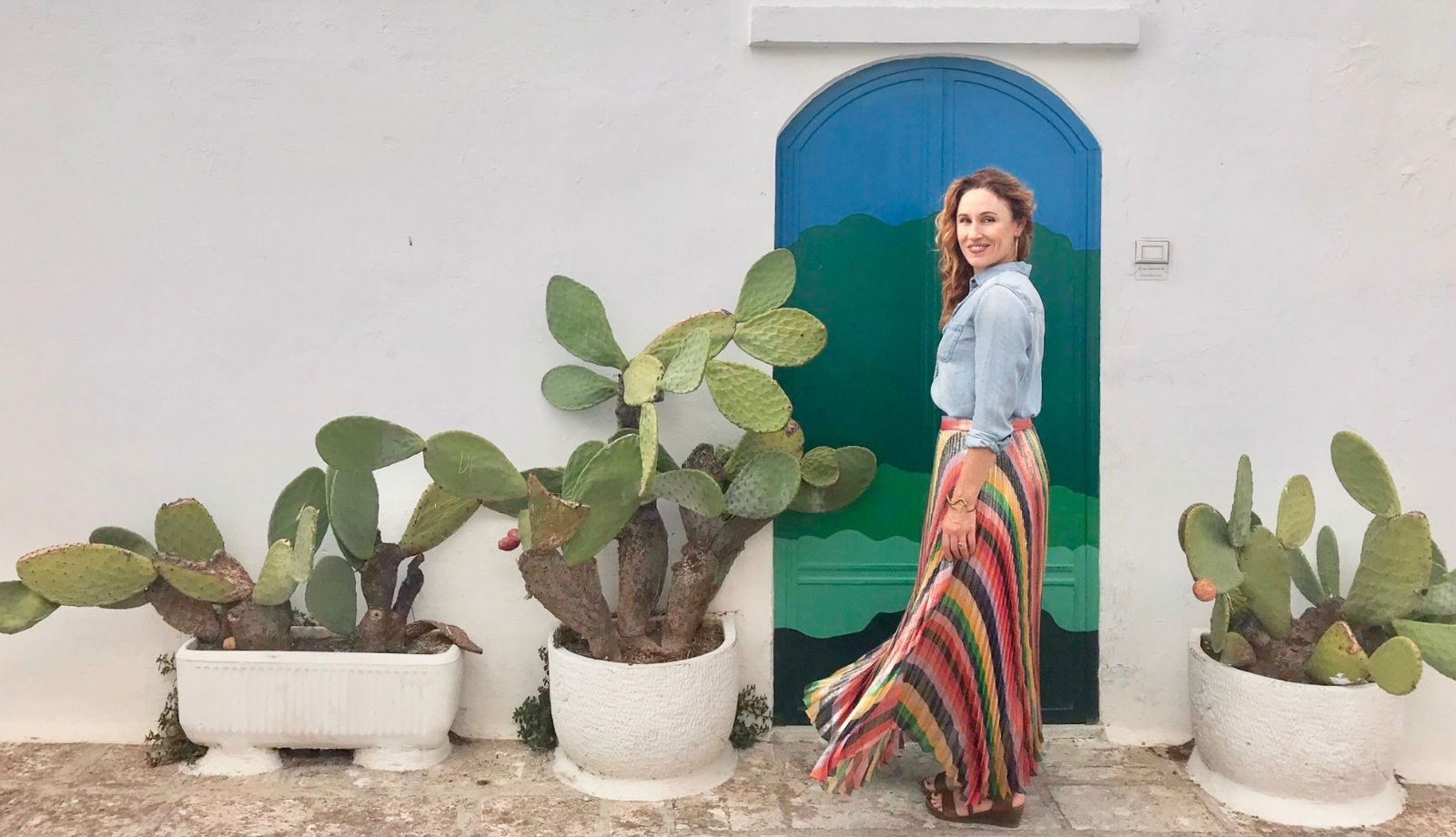 Woman in rainbow colored skirt in front of prickly pear cactus and white adobe wall
