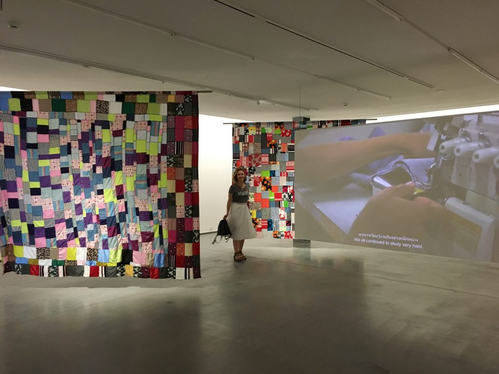 Woman in a white skirt standing amongst a modern art installation of hanging textiles and video media
