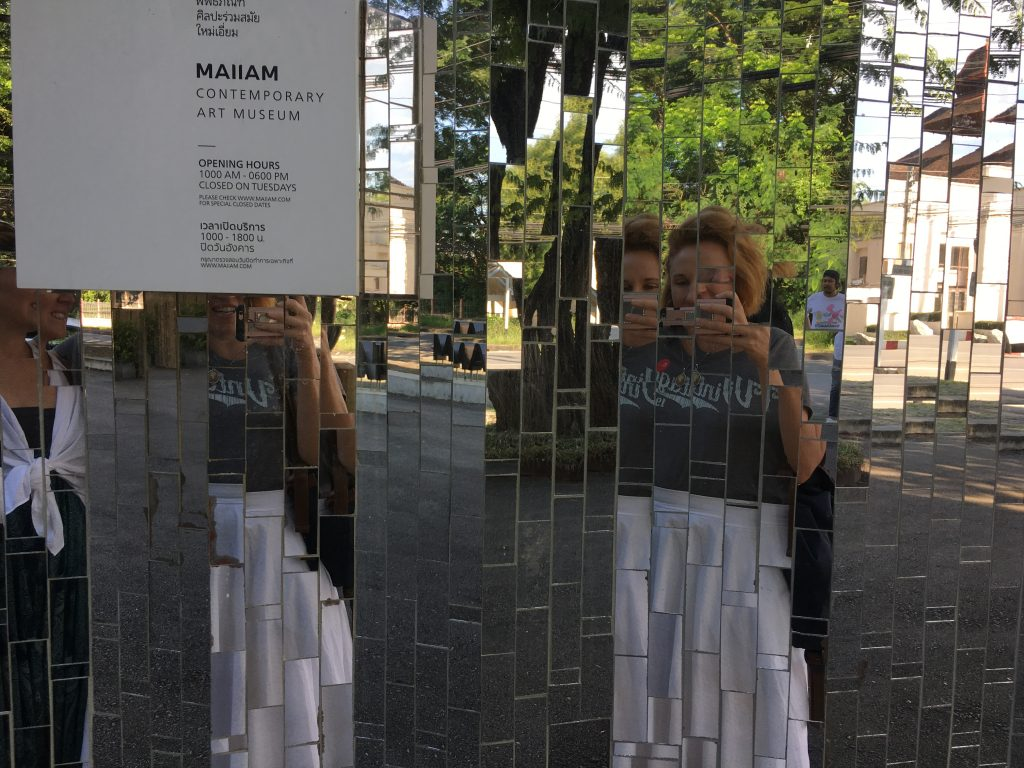 Reflective selfie in front of Maiiam museum's mirrored exterior
