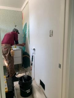 white man in red shirt installing wallpaper on a white wall.
