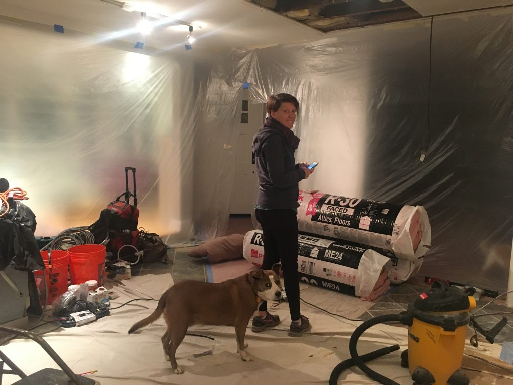 Photo of a woman and a dog standing in the middle of a gutted kitchen, surrounded by plastic sheeting