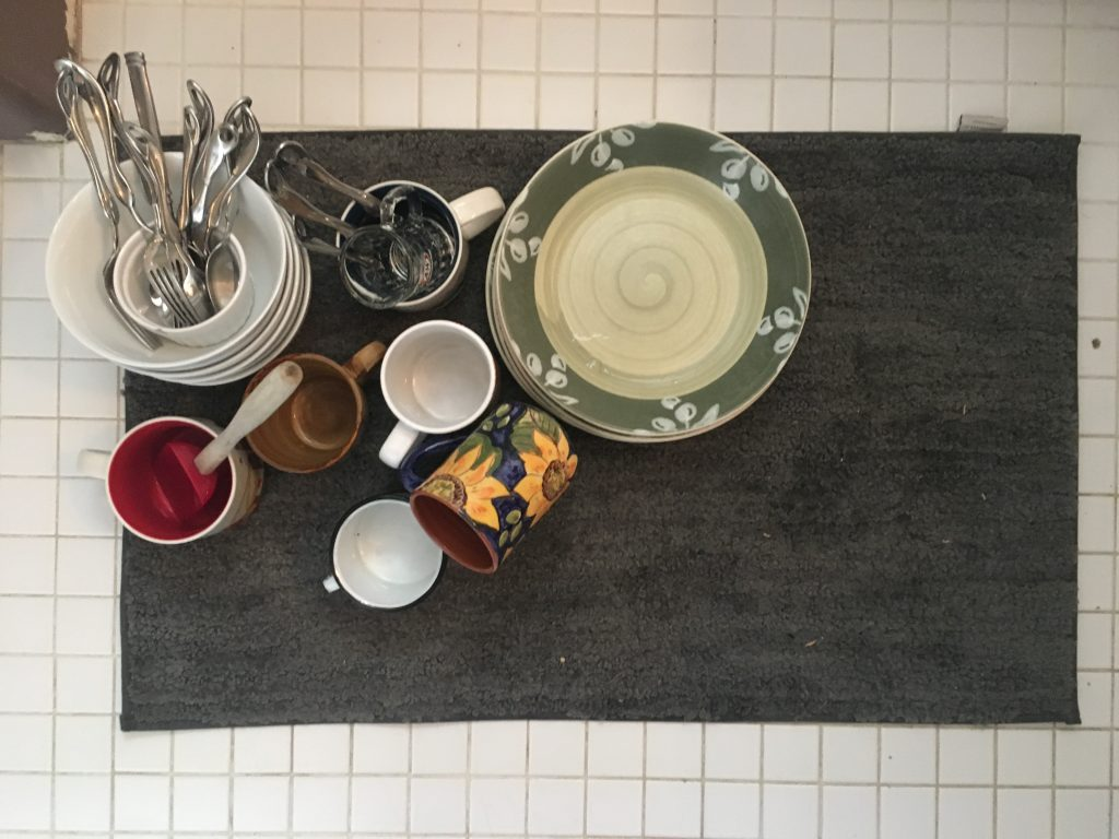 photo of dishes sitting on a bathmat on the floor