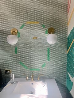 green tape measures out potential mirror sizes between two midcentury modern bathroom wall sconces