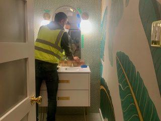 A man in a neon green vest installs a mirror over a bathroom vanity