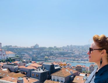 Annie with a puffy ponytail in her hair stands in profile in front of a view of the city of Porto and the Rio Duoro.