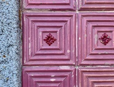 Fucshia square patterned tiles with a red diamond design in the center of each tile. Wall tiles are bordered by speckled grey cement.