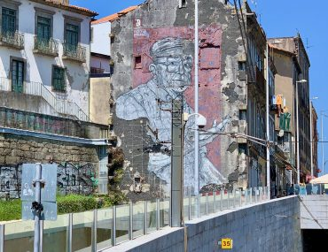 A mural of a Portuguese fisherman is depicted in soft pink against the side of a crumbling building. A train track dips down the front side of the photo.