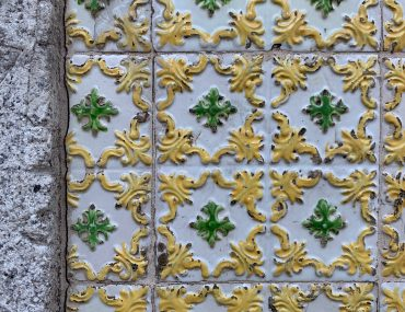 Yellow, white and green architectural wall tile with a curling baroque motif.
