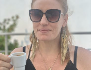 Annie in a black tank dress and gold feathery earrings and black sunglasses cheersing with a white espresso cup.