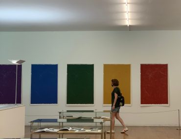 Tiffany walking in front of five solid color panels in the color of the rainbow. In the foreground are art books. The gallery walls are white and the floors are oak.