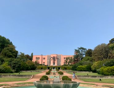 The Casa de Serralves, a pink art deco building in the Serralves art complex. A giant spider sculpture stands in front of the house, and a cascading water feature is in the foreground.