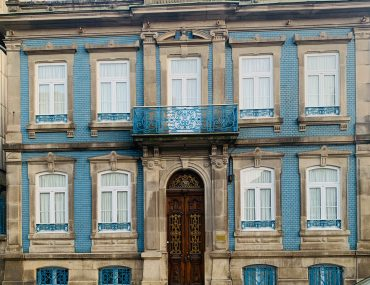 Stone and blue tile two story house in Porto with a large, wood arched doorway.