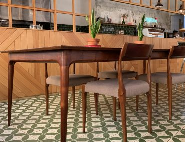 An interior decor shot of a mid-century modern decorated coffee shop with green and white patterned tiles and wood tables.