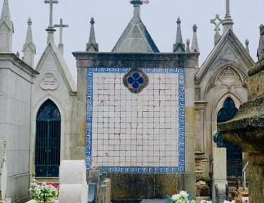 Masuloleum with a white tile facade and blue tile trim. Surrounded by cross-topped stone masoleums and the sky is grey and overcast.