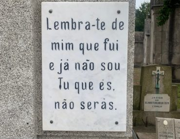A cemetery sign reads a epitaph for a Portuguese against a stone mausoleum. A grey sky is in the background.
