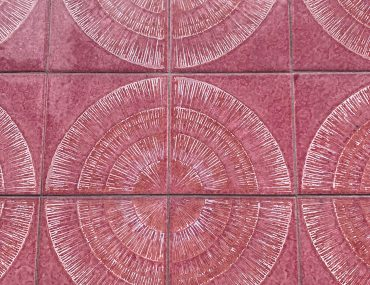 Pink sunburst shaped wall tiles bordered by faded concrete.