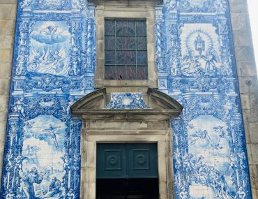 Blue and white handpainted tile churc with religious scenes depicted in the tiles. A family of four stands posed in front of the tile wall, showing the grandeur of the building size.