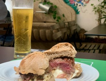 Closeup of a prego sandwhich--white cheese, beef, and bread. A cold beer and a painted mural are in the background.