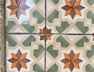 beautiful sage green, white, orange, and purple tile in a repeating geometric star pattern.