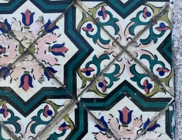 Emerald green, pink, and blue flower star hand painted tiles. The tiles have chips and show signs of age.