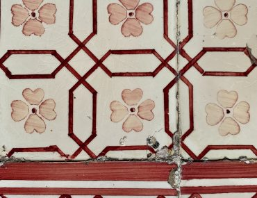 Faded red to pink wall tiles showing a mix of flowers and geometric rectangular patterns. Chips are visible in the wall tiles.
