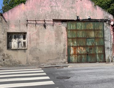 An old pink garage is faded with a faded metal sliding barn door. The sky behind is bright blue.