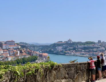 A view from Gaia across the river Duoro toward the Ponte de Luis the 2nd. Three people in shorts and hats look out over a balustrade.