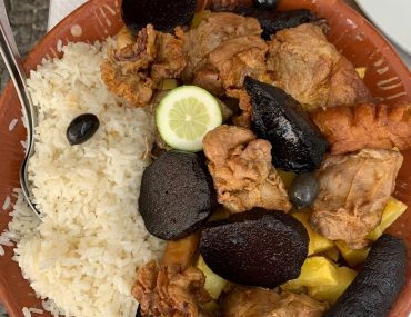 A terracotta plate full of rice, blood sausage, fried pork innards, and potatoes sits on a white table cloth.