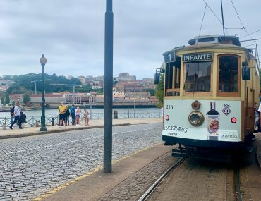 """Electric tram with a sign reading """"Infante"""" on a two-rail track with the river behind. The sky is overcast."""