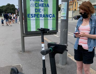Tiffany standing in front of green and white striped sign with portuguese wording using a smartphone app to activate an electric scooter.