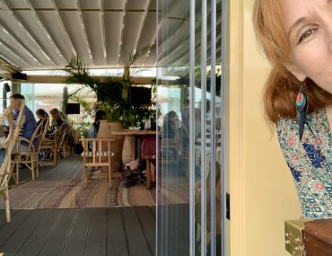 Annie's head leaning into a open-air beachy restaurant scene with boho decor.