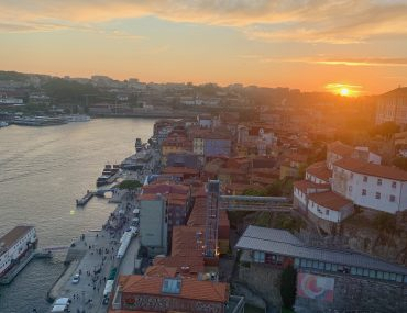 View over the city of Porto as the sun sets in the west like a golden ball on the horizon.