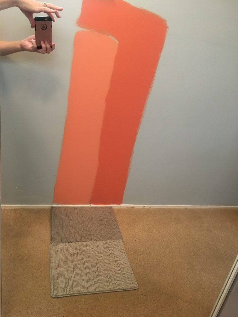 coral colored paint swatches painted on a light blue wall. Grey carpet samples against a brown carpet.