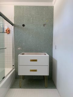 white bathroom vanity in a partially remodeled bathroom with green penny tile backdrop