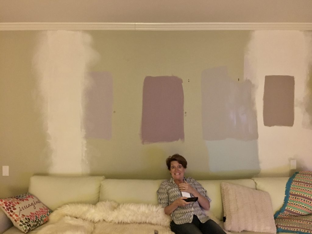 woman making a silly face in front of multiple paint swatches painted on a wall