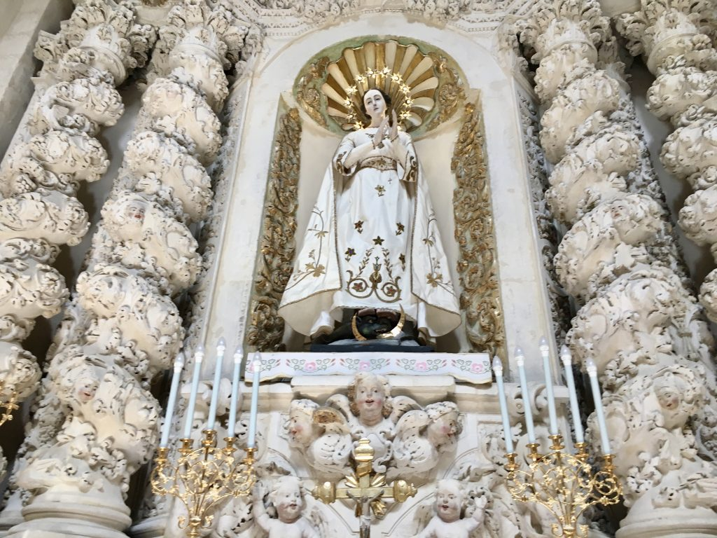 photo of a female saint statue carved of white stone in a church