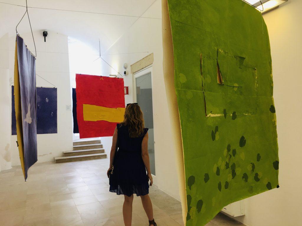 woman in a purple dress walking through an art gallery