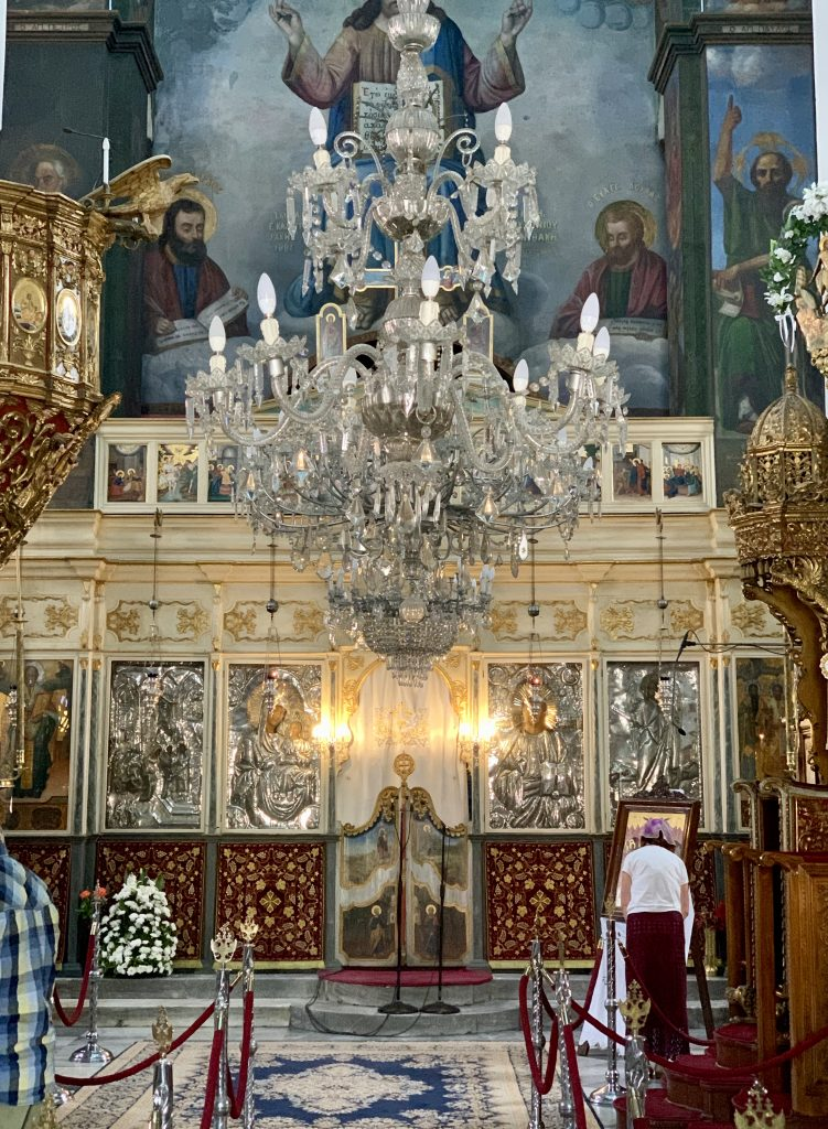 interior of a Byzantine church with large chandelier and a woman praying
