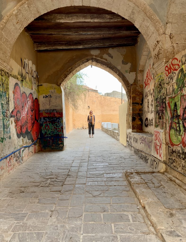 a woman standing on a street, framed by an arch with graffiti on it