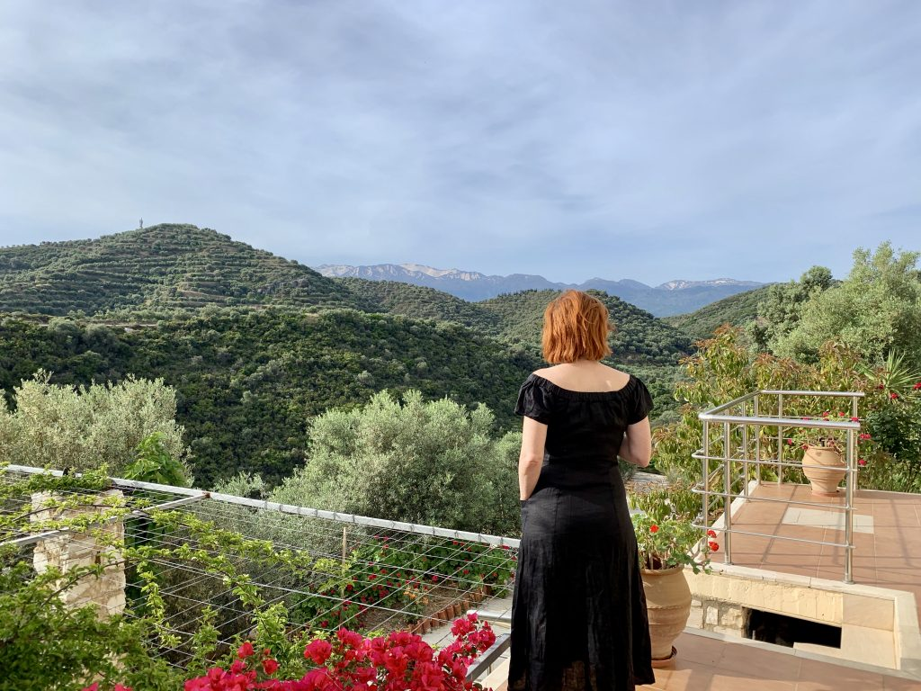 woman looking out over green mountain tops wearing a black dress