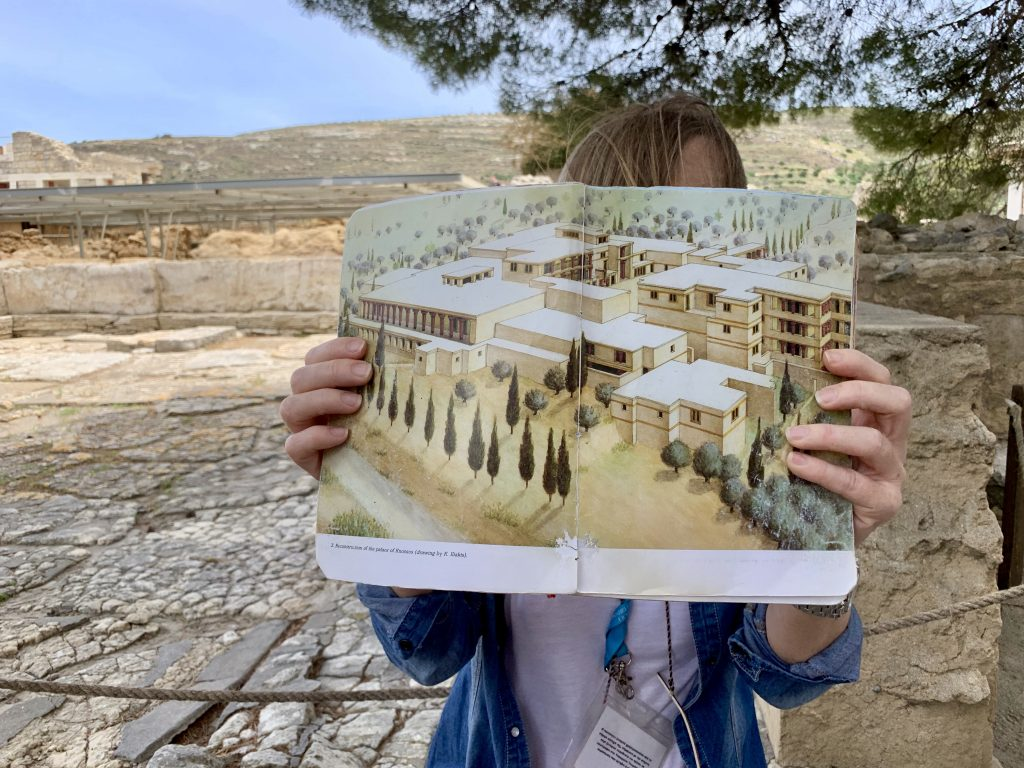 woman holding a map of palace of knossos at the archaeological site