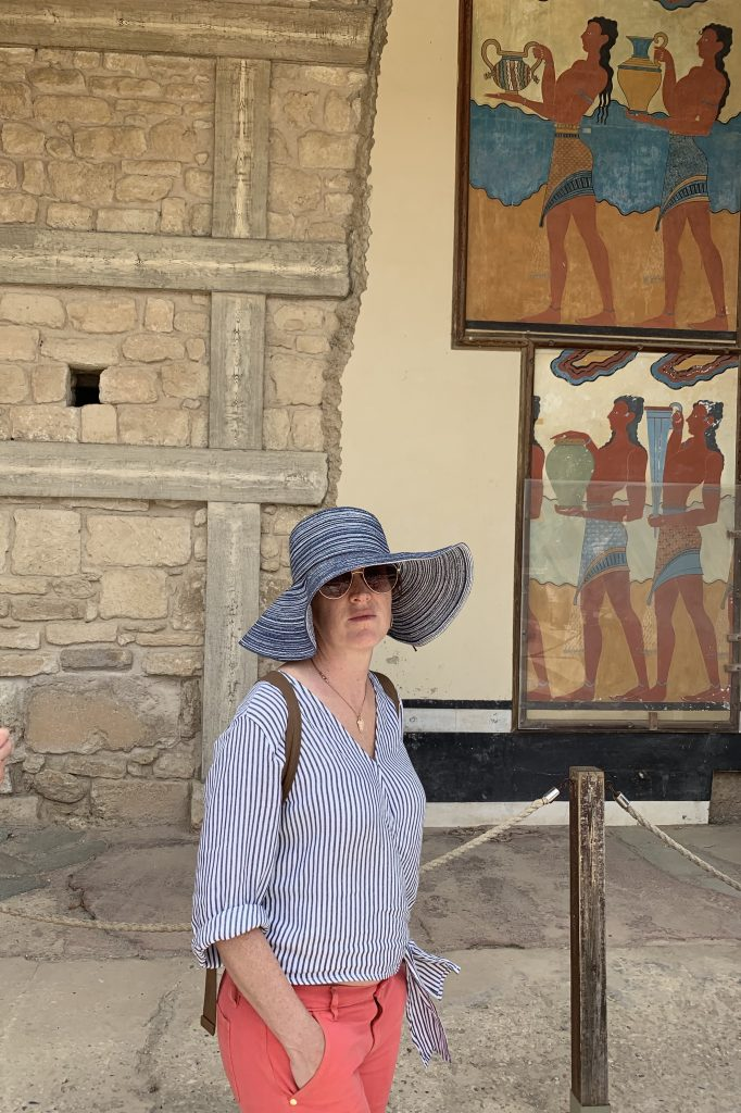woman in blue hat in front of a mural of ancient minoans