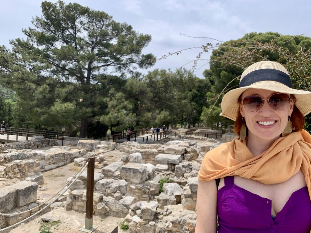 smiling woman in hat standing in front of ancient ruins