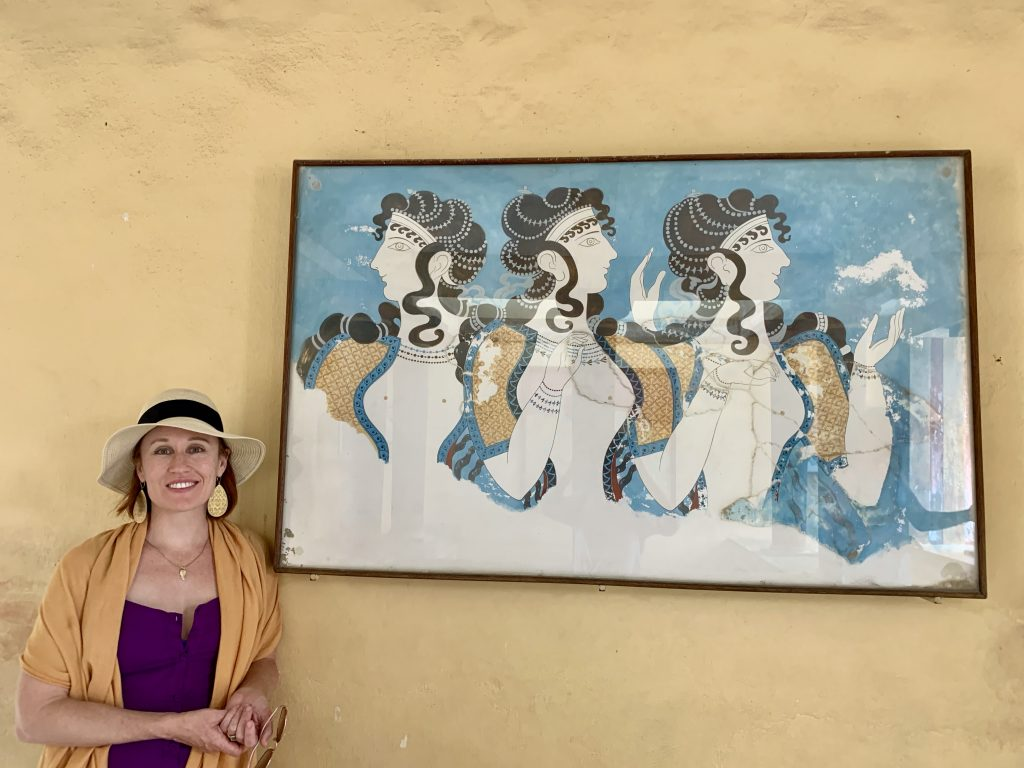 smiling woman standing in front of a mural of three women