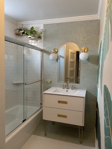 White bathroom remodel with brass planter boxes hanging above the shower wall.